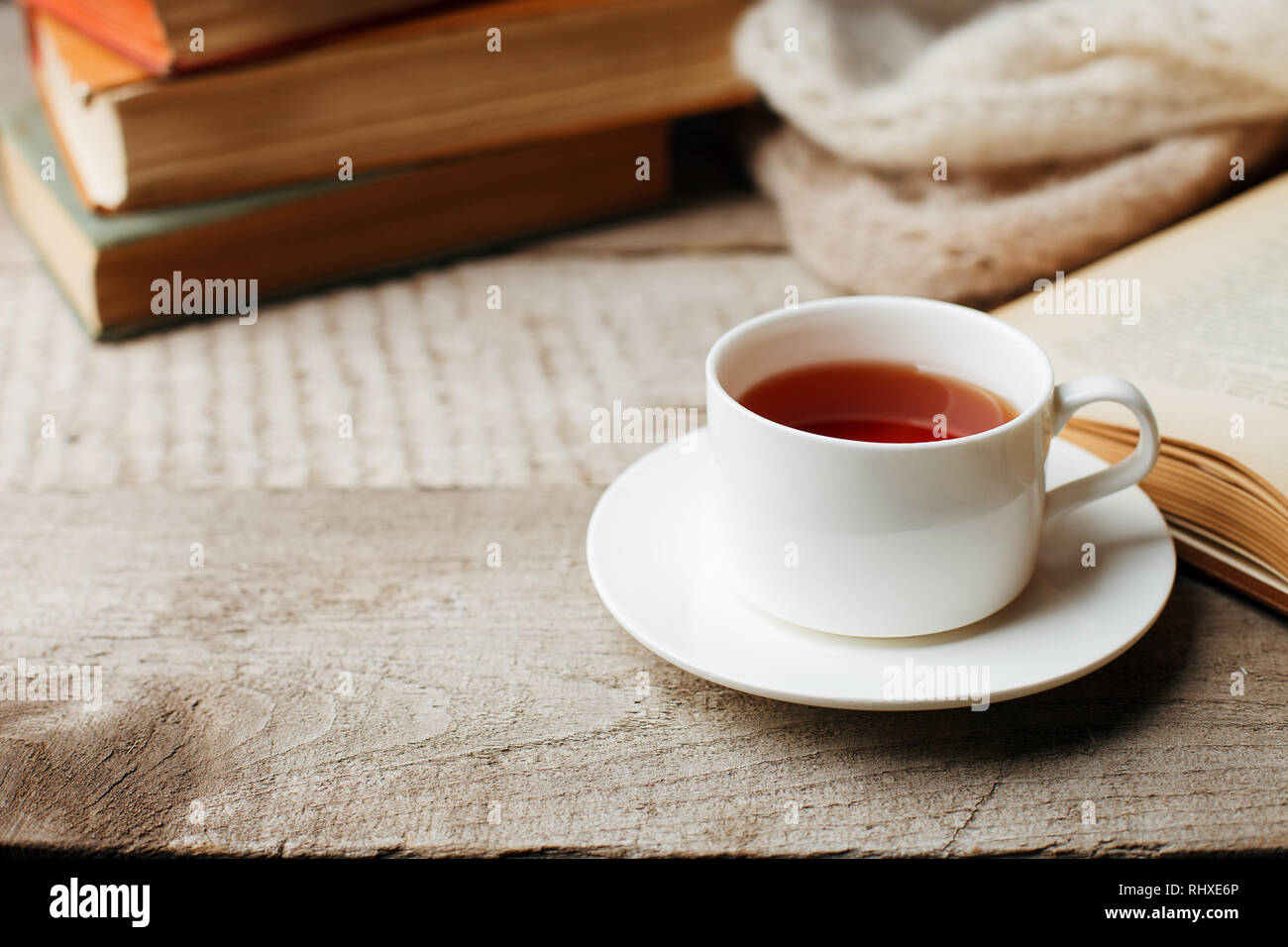 Valentines day concept with tea cup and books on wooden vintage background, cozy weekend, hygge leisure concept - Stock Image