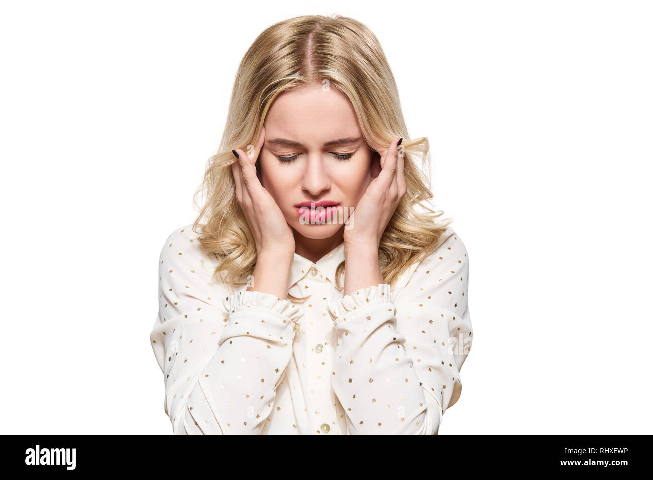 Young Woman Having Headache. Stressed Exhausted Young Woman massaging her temples. Woman Suffering From Migraine, Feeling Pressure And Stress. - Stock Image