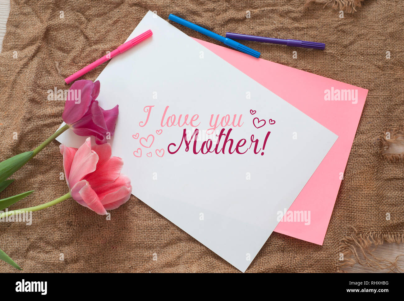 Two tulips with Scilla bifolia and blank notepad with colored pens on a sackcloth texture. I love you mother. Woman International Day Stock Photo