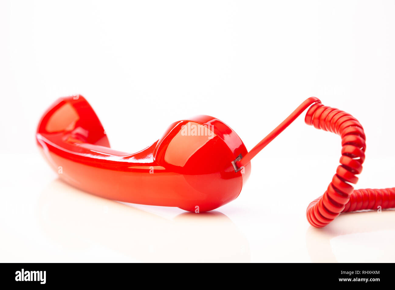 A red retro telephone handset lying on it's side against a white background. - Stock Image