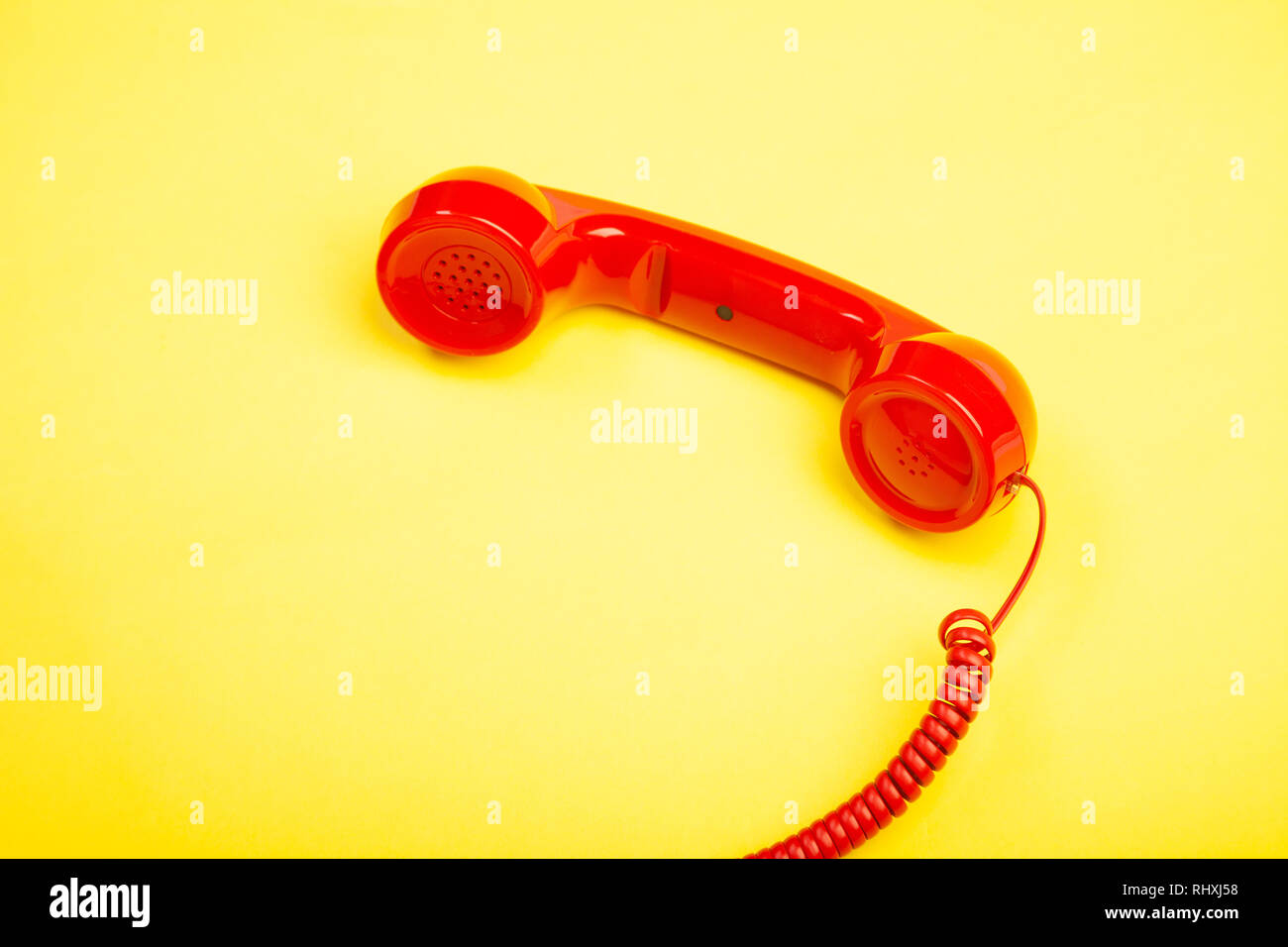 A red retro telephone handset lying on it's side against a yellow background. - Stock Image