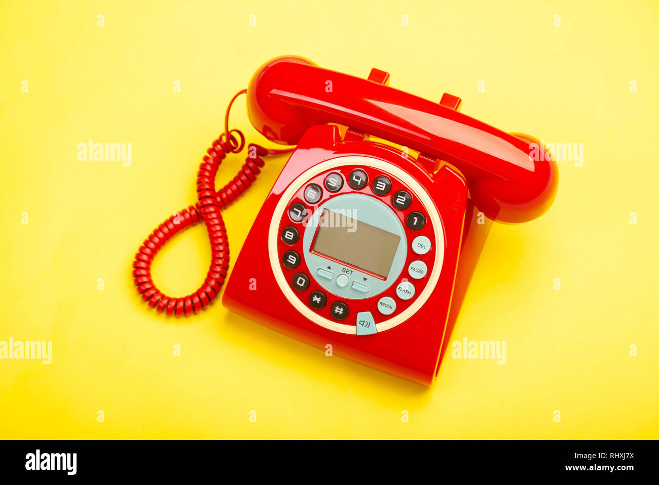 A red retro telephone from above against a yellow background. Stock Photo