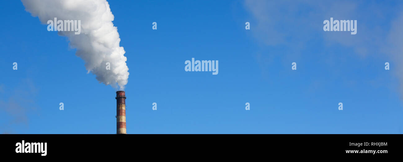 White smoke comes from pipes against blue sky Stock Photo