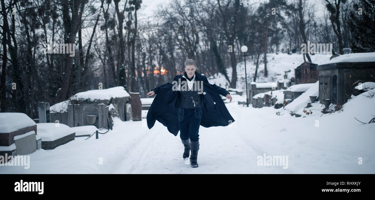Young man in image of black magician runs on snow background. - Stock Image