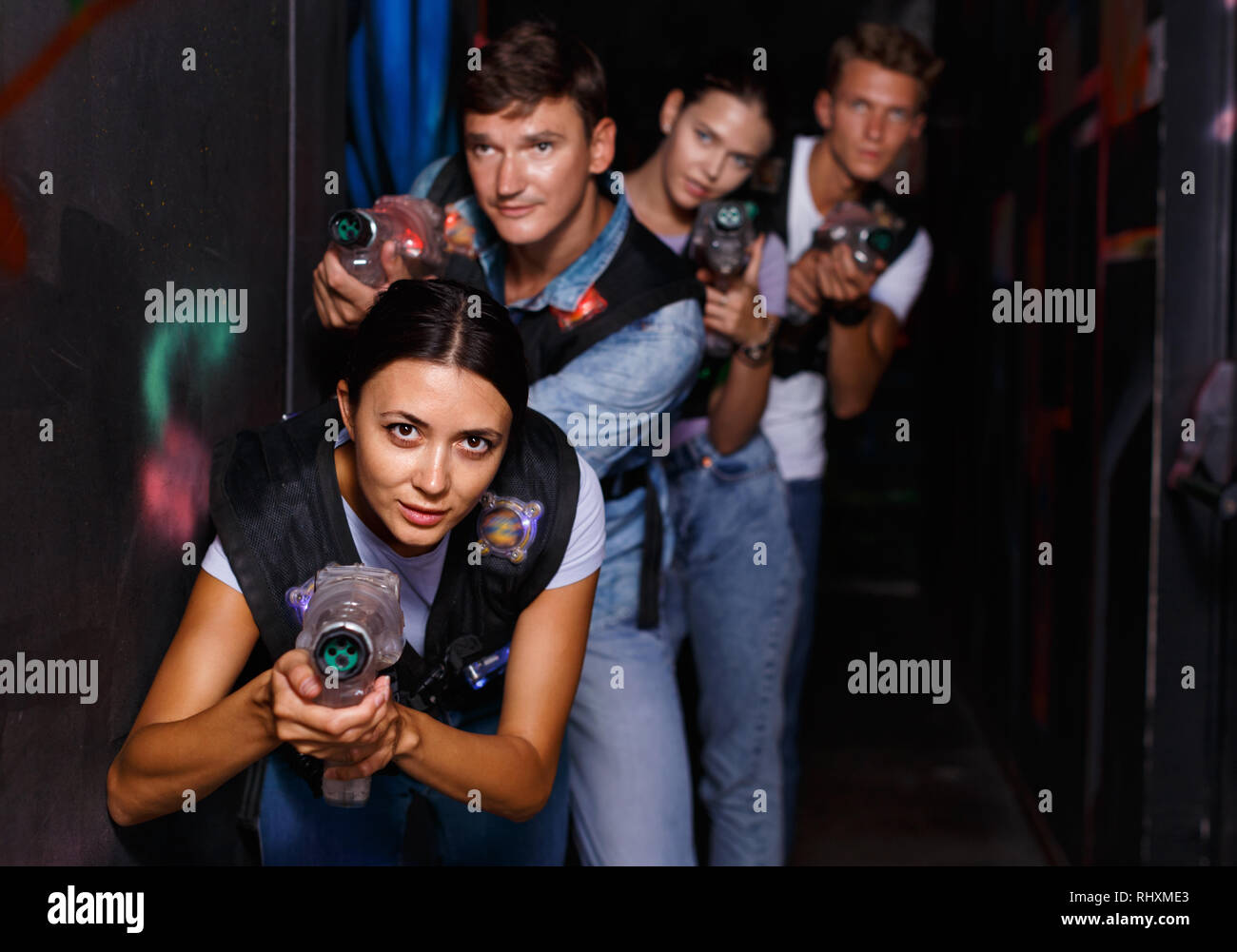 Portrait of happy cheerful glad young friends playing laser tag game