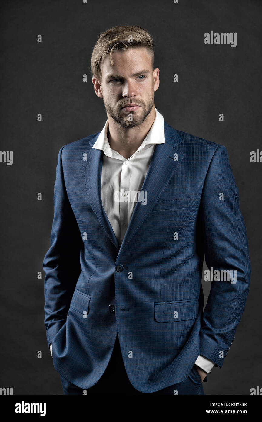 Businessman attractive cares about appearance. Man bearded strict face with hairstyle, dark background. Masculinity concept. Man bearded unshaven guy looks handsome well groomed in formal wear. - Stock Image