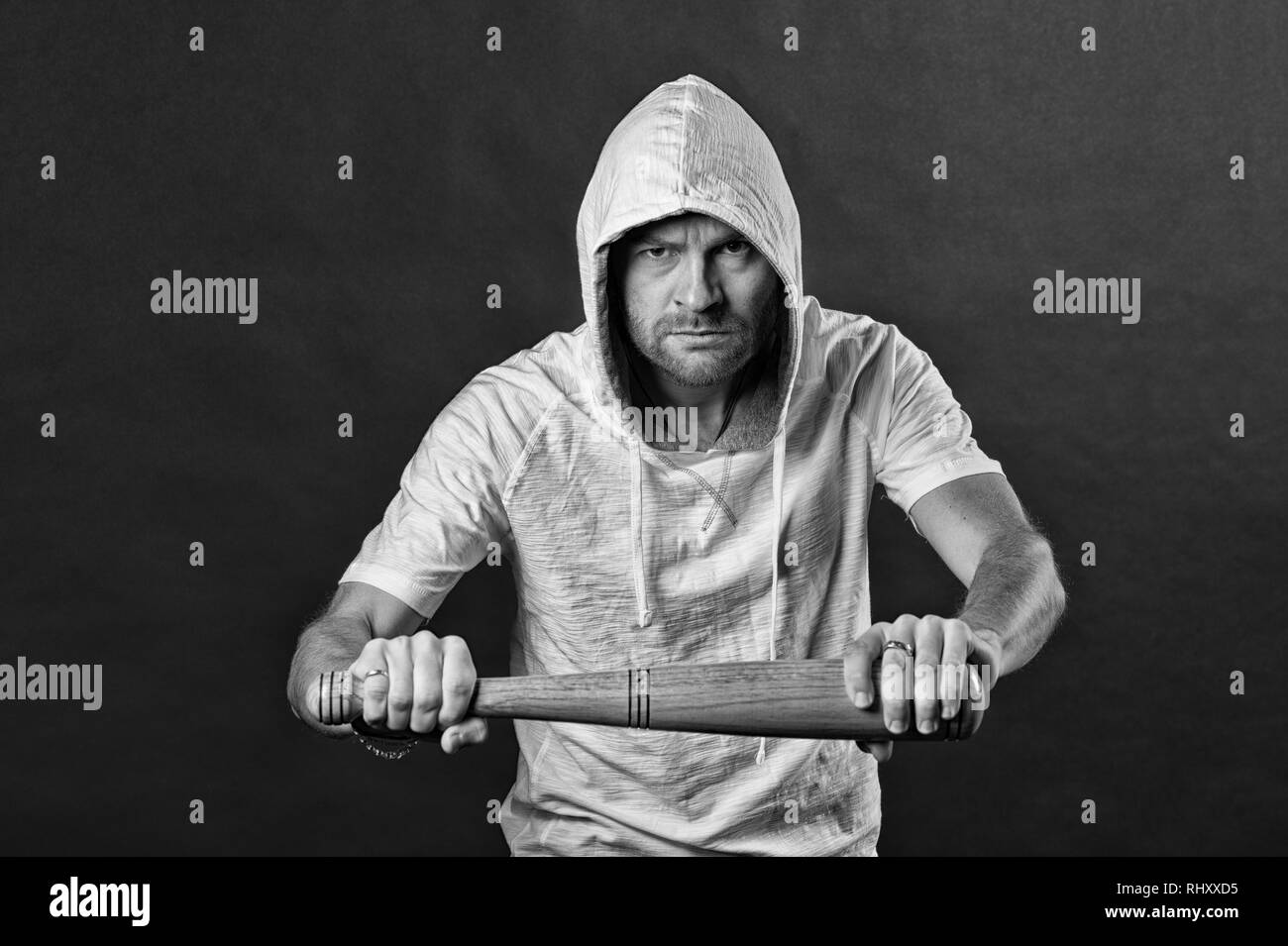Gangster hold baseball bat. Hooligan wear hood in hoodie tshirt. Bearded man threaten with bat weapon. Aggression or anger and violence concept, black and white. - Stock Image