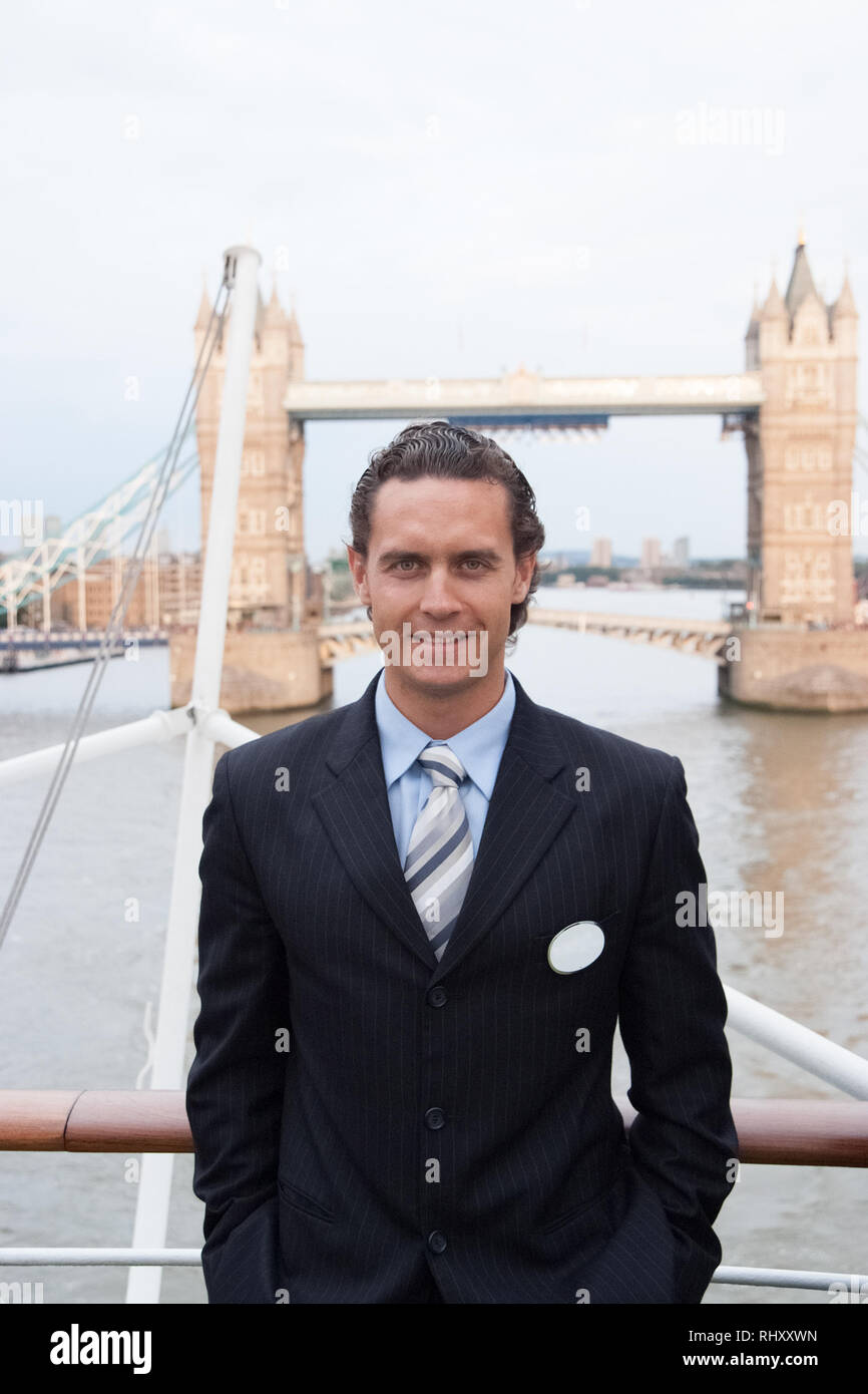 Happy businessman in London, United Kingdom. Man smile at Tower bridge. Tourist enjoy sightseeing in city. Travelling for business and pleasure. Architecture and design concept. - Stock Image