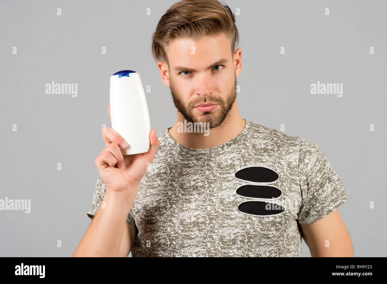 Man enjoy freshness after washing hair with shampoo. Guy with hairstyle holds bottle shampoo, copy space. Hair care and beauty supplies concept. Man strict face holds shampoo bottle, grey background. Stock Photo