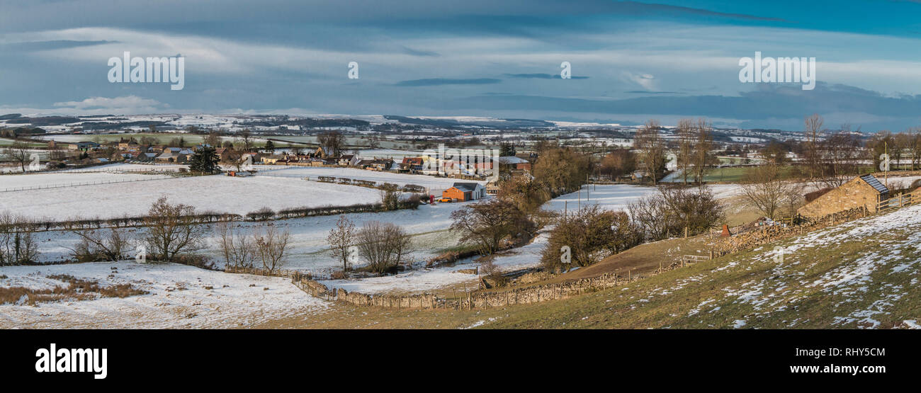 Teesdale landscape, panoramic view over the rural village of Hutton Magna towards Barningham Moor with snow covered fields, dark sky and sunshine - Stock Image