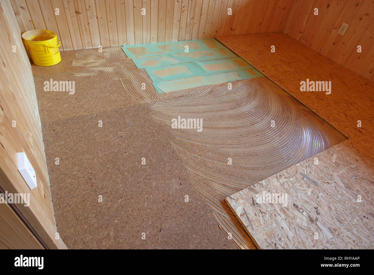Laying of new parquet flooring in progress, adhesive primer spread on old floor. Professional work in progress, home improvement and renovation, carpe - Stock Image