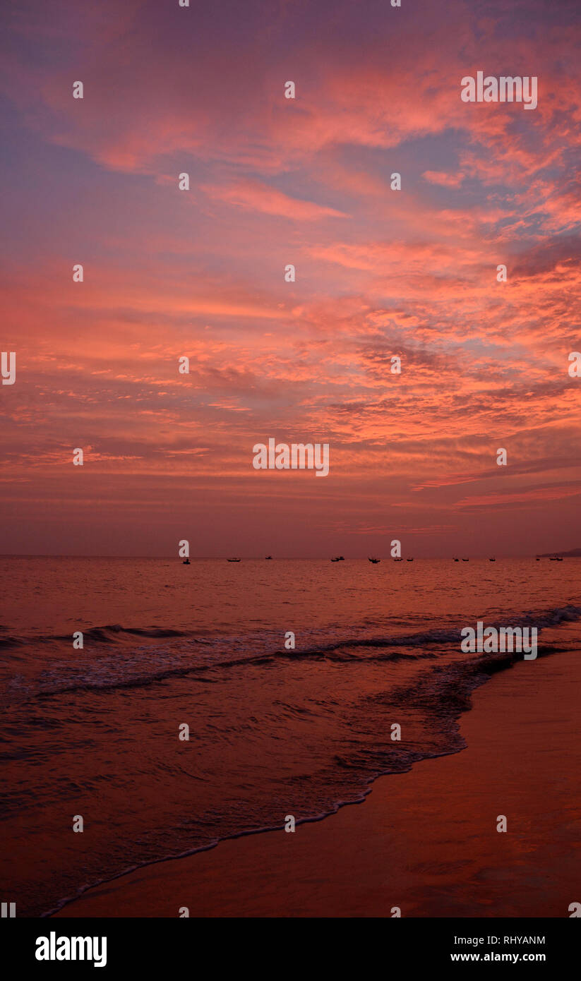 Sunset over the water off the coast of the beach at Mui Ne in central south Binh Thuan Province, Vietnam - Stock Image