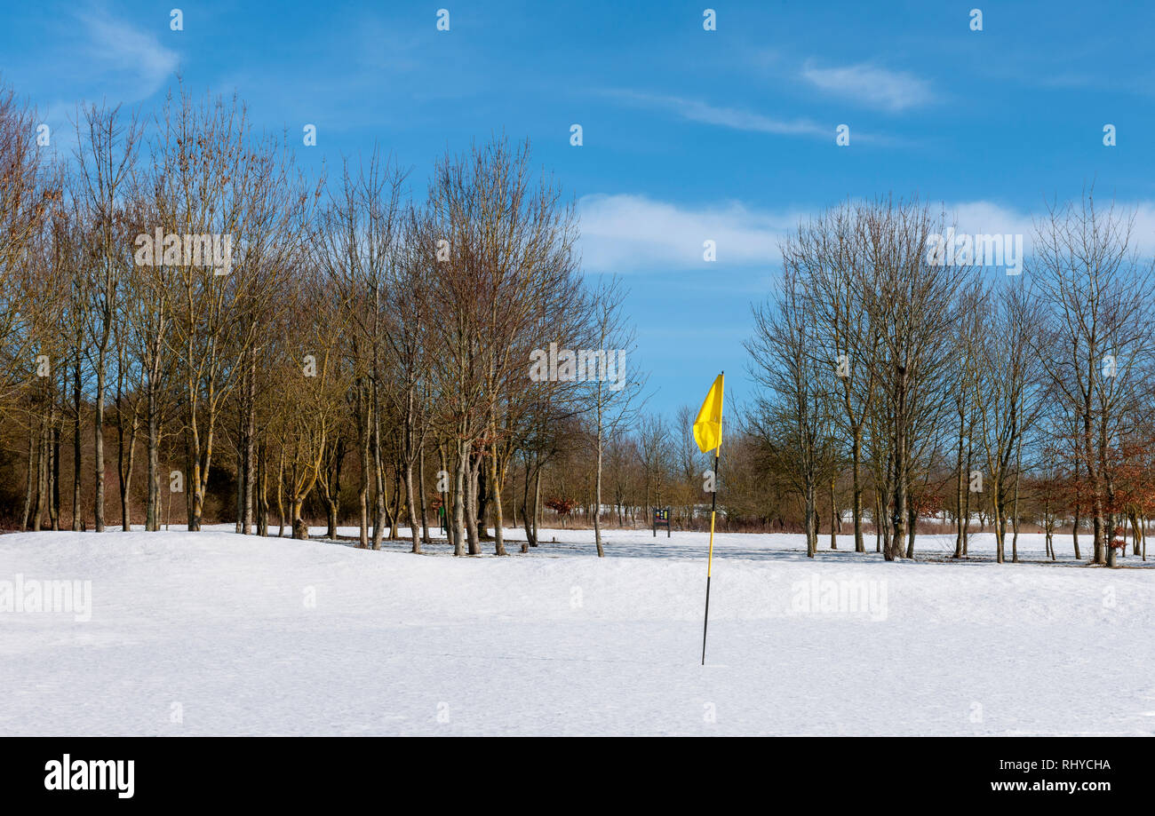 Snow covered putting green at The Hampshire Golf Course, Andover, Hampshire, England, UK - Stock Image