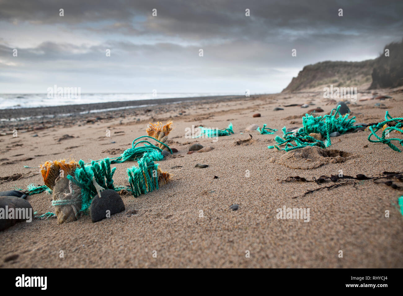 Discarded fishing nets embedded in sand on UK beach a major form of plastic pollution. - Stock Image