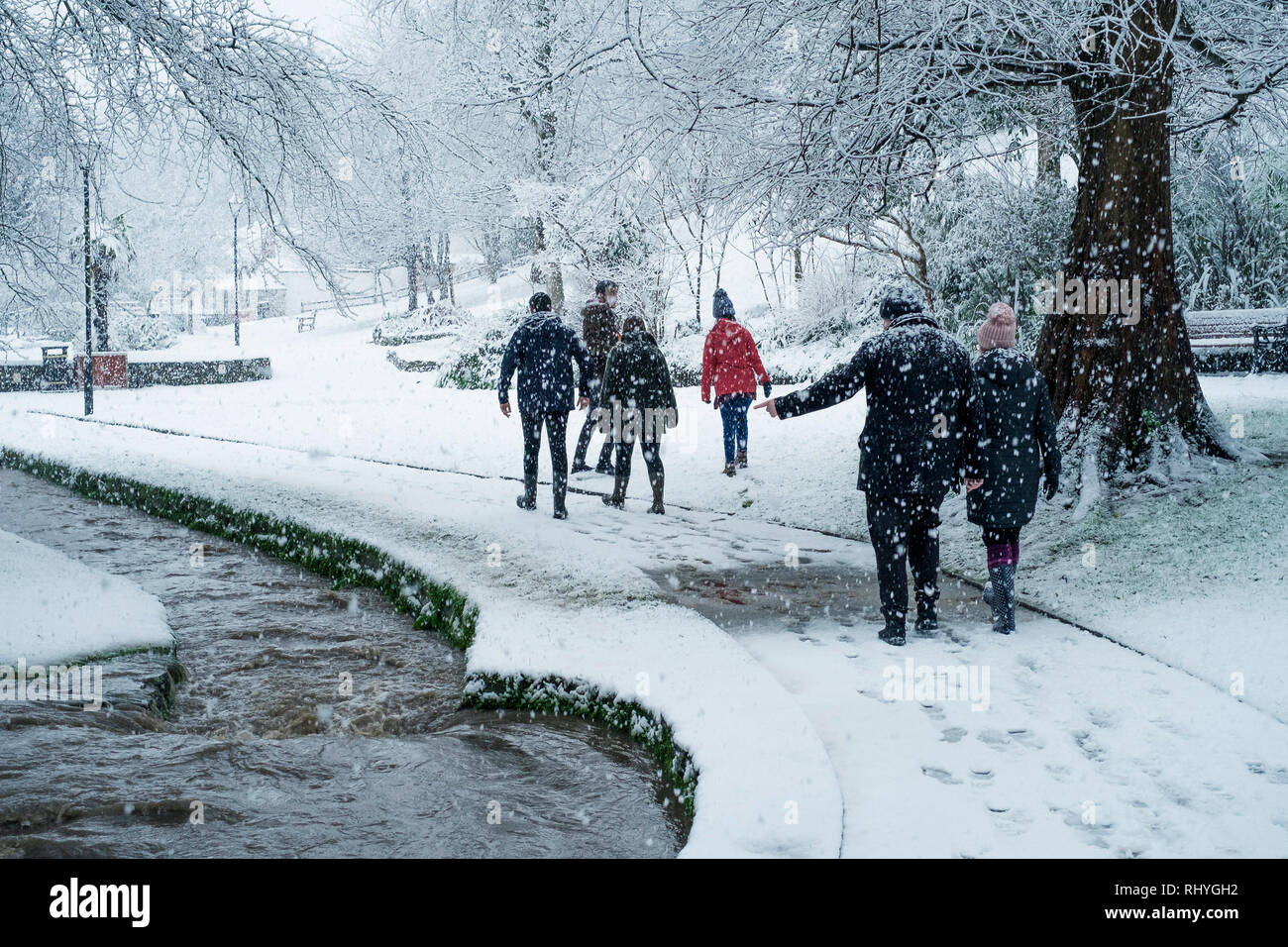 People enjoying walking through heavy snowfall in Trenance Park in Newquay in Cornwall. - Stock Image
