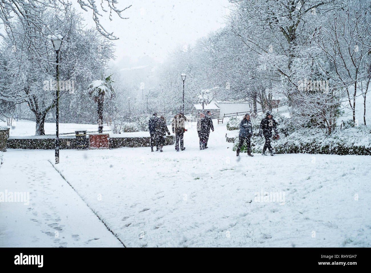 People walking through heavy snowfall in Trenance Park in Newquay in Cornwall. - Stock Image