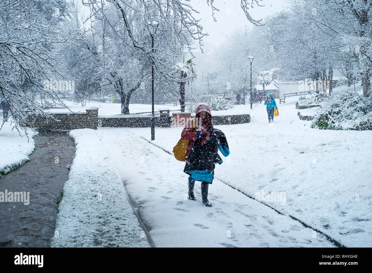 People walking through Trenance Gardens in heavy snowfall in Trenance Park in Newquay in Cornwall. - Stock Image
