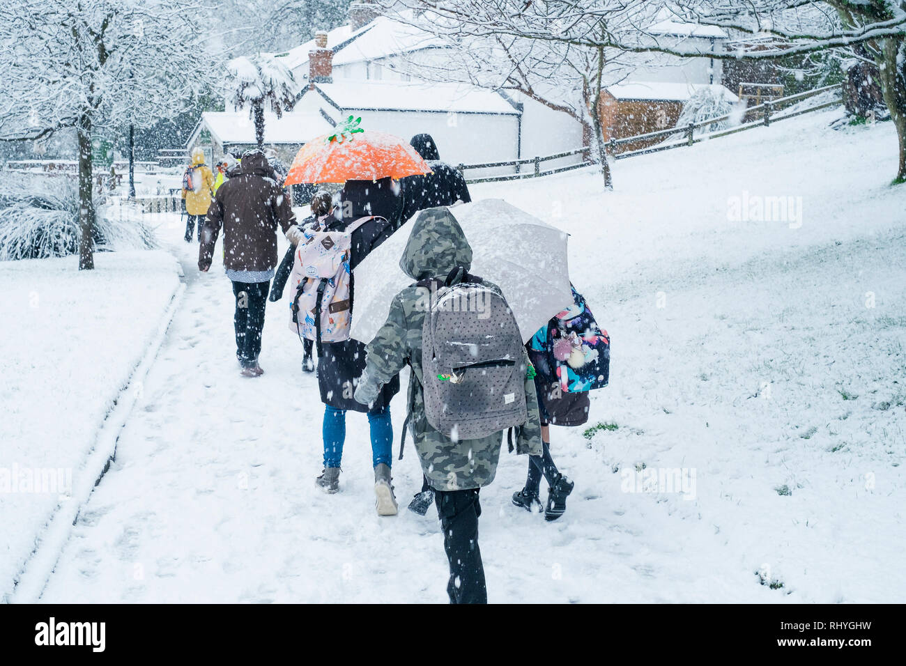 People walking through Trenance Gardens in heavy snowfall in Newquay in Cornwall. - Stock Image