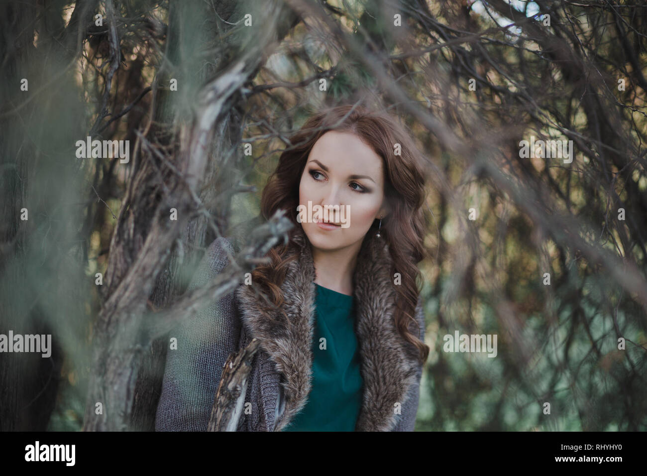 Beautiful genuine lady mystic with curly brunette hairs and adorable eyes dressed in fancy stylish warm clothes with fur on neck lonely posing sit for - Stock Image