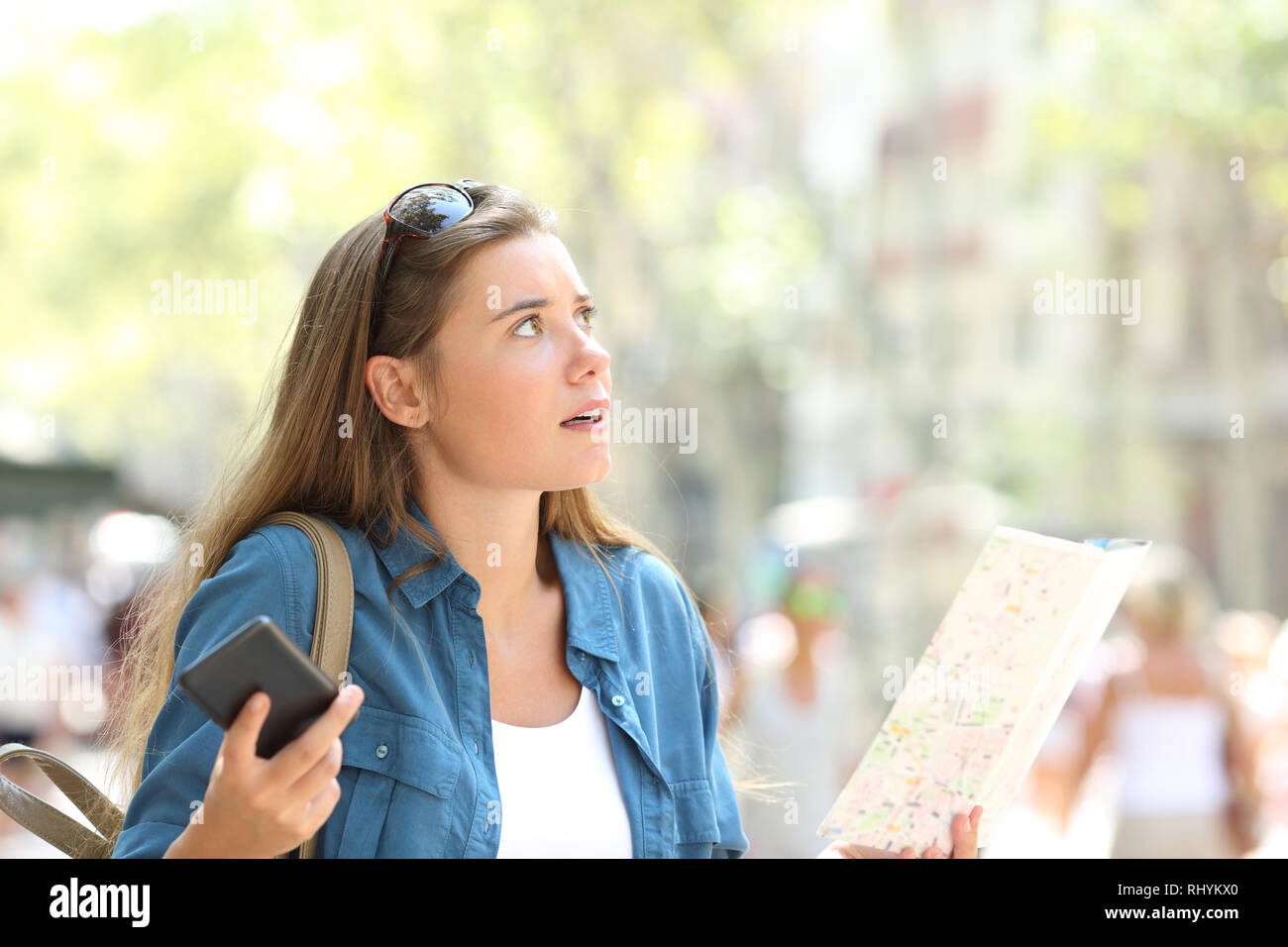 Lost tourist trying to find location holding phone and paper map in the street - Stock Image