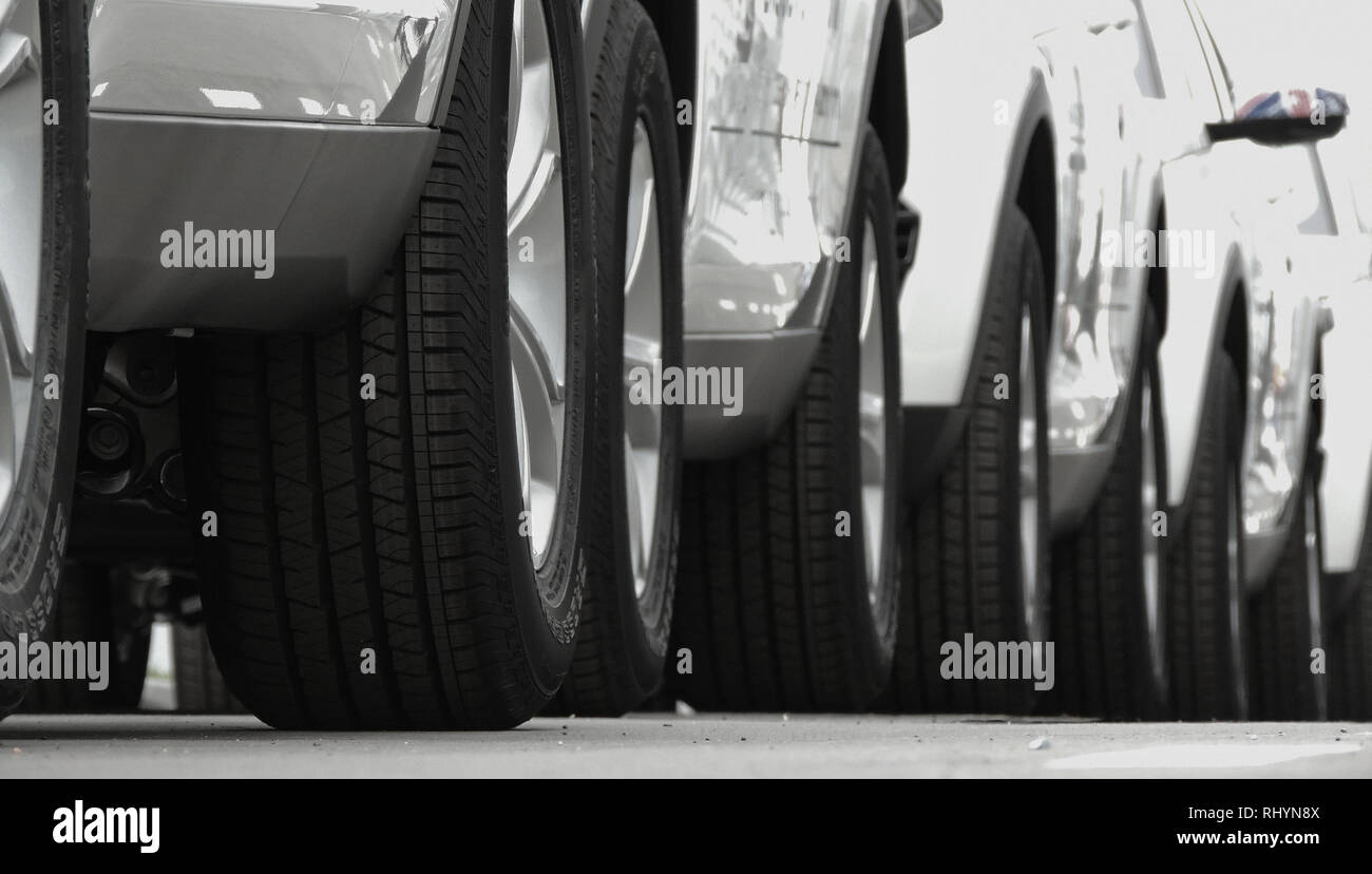 Line of the wheels of same vehicles staying on the road - Stock Image