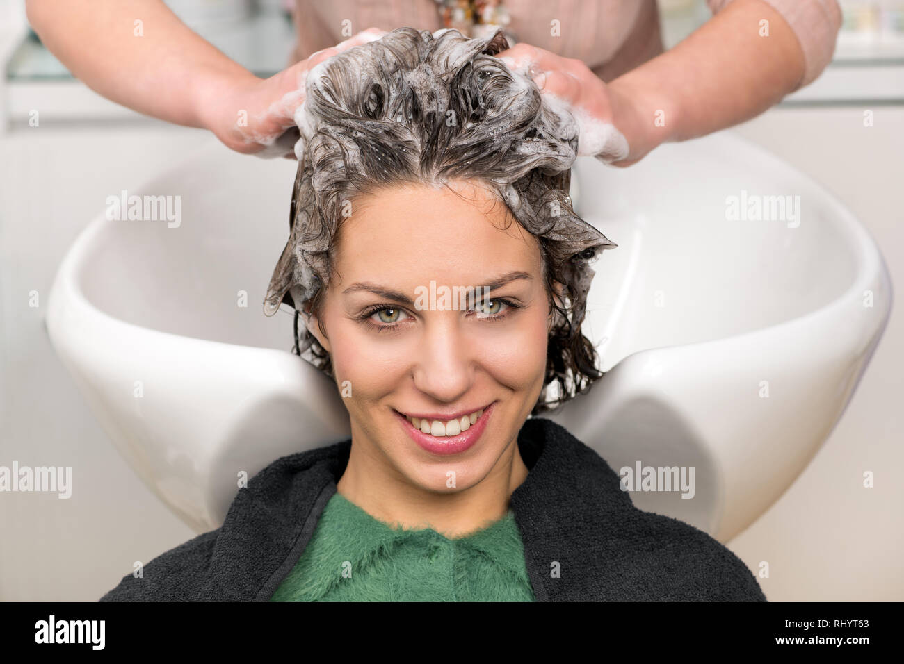 Cute young girl having her hair washed with shampoo by the hands of professional hairdresser at beauty salon, leaning back on white ceramic hair wash  - Stock Image