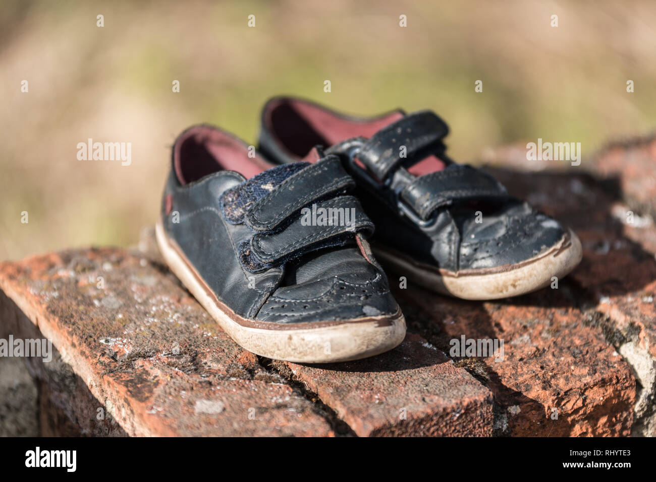 One pair of lost, abandoned kid shoes can symbol some missing child, one pair of kid shoes on a brick wall - Stock Image