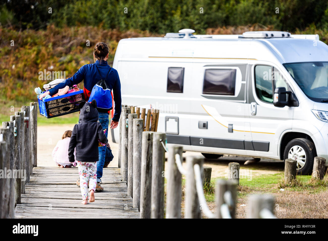 Family walking to camper van with box of toys. Family is returning from playing on the beach. Walking towards motorhome on wooden pathway over sand du - Stock Image