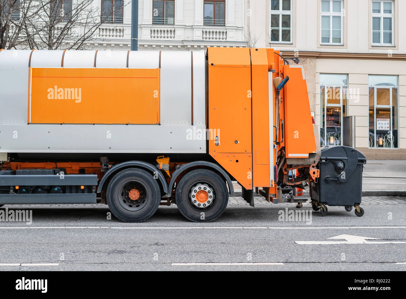 Garbage disposal lorry at city street. Waste dump truck on town road. Municipal and urban services. Waste management, disposal and recycling. Mock-up Stock Photo
