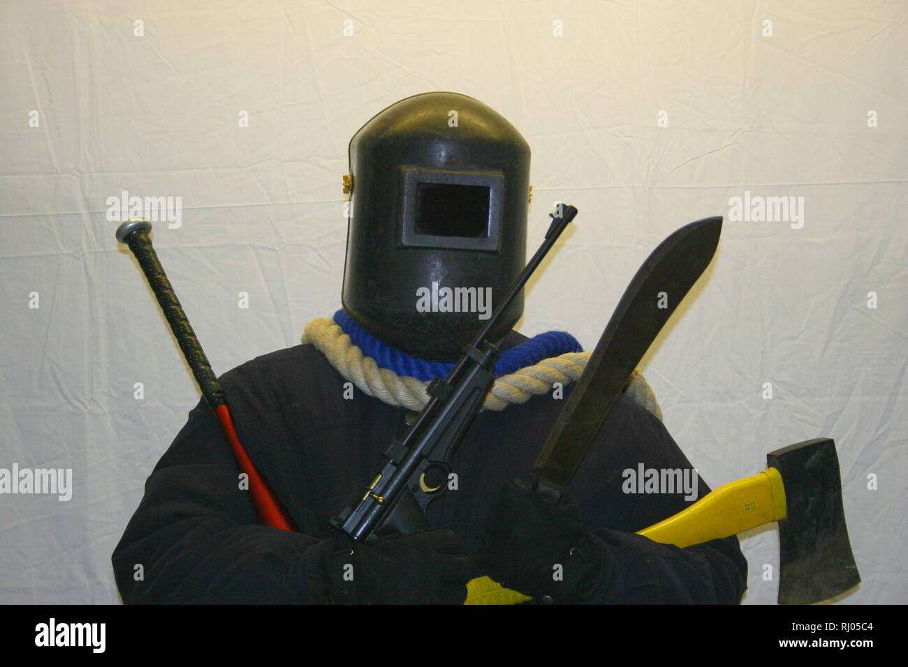 Weapons. Knife crime. Knives. Guns. Rifle. Air weapons. Blunt instrument. Baseball bat. Axe. Machete. Rope. Heavily armed man. Face covering. Anonymity. Violent society. Sick society. Concepts. Conceptual. Education. Mask. Welders mask. Going equipped. Tooled up. Offensive weapons Gangs. Armed gangs. Book cover. Stock Photo