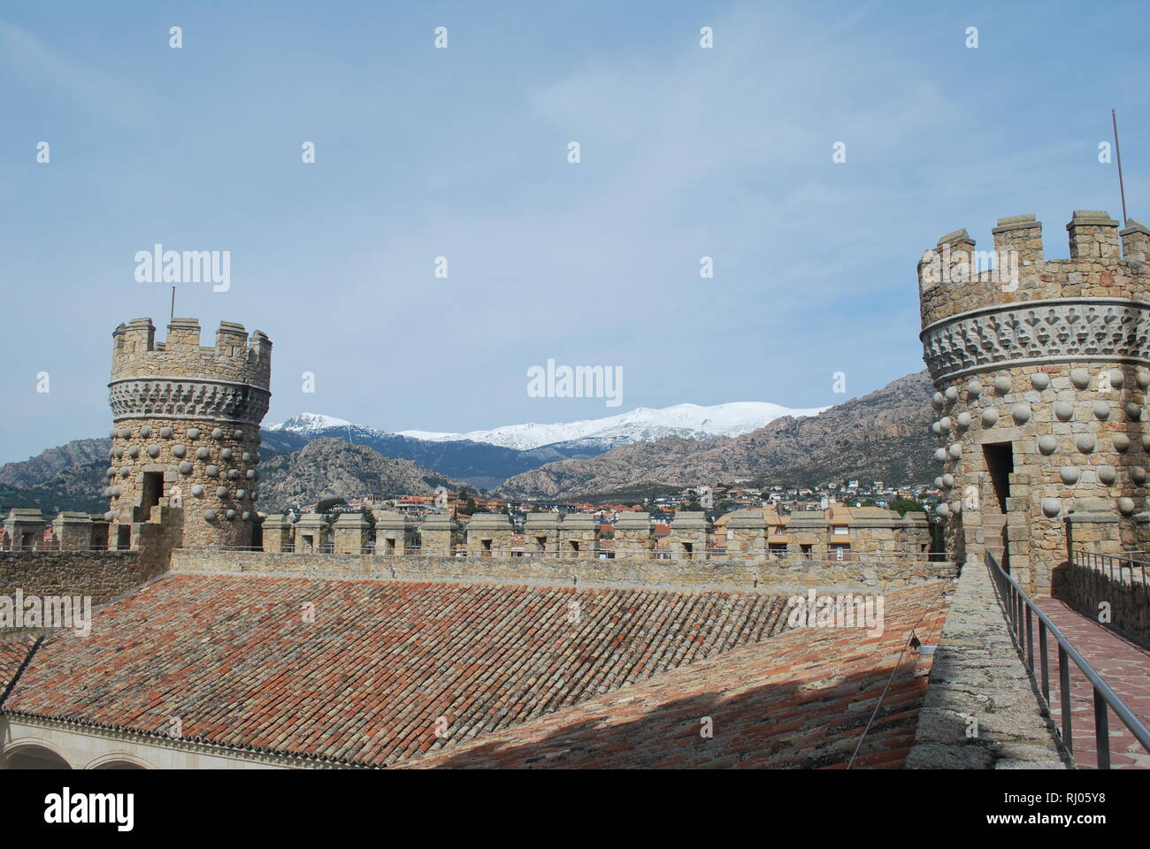 A view of mountains and turrets on the rooftop terrace of the castle of Manzanares el Real in central Spain Stock Photo