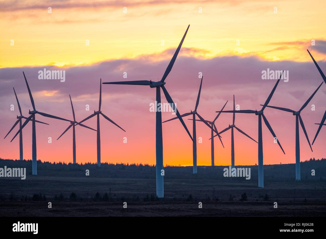 The sun sets behind Black Law wind farm near Forth, South Lanarkshire, Scotland. - Stock Image