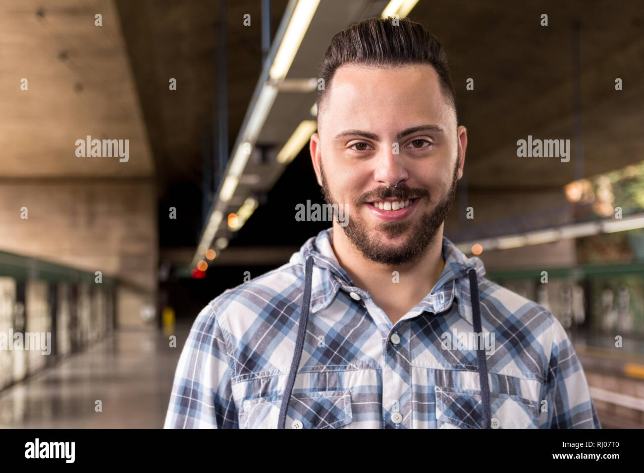 c0fefc24 Portrait of Young bearded man wearing plaid shirt waiting for train at tube  subway station. Concept of commute, transport service, mobility.