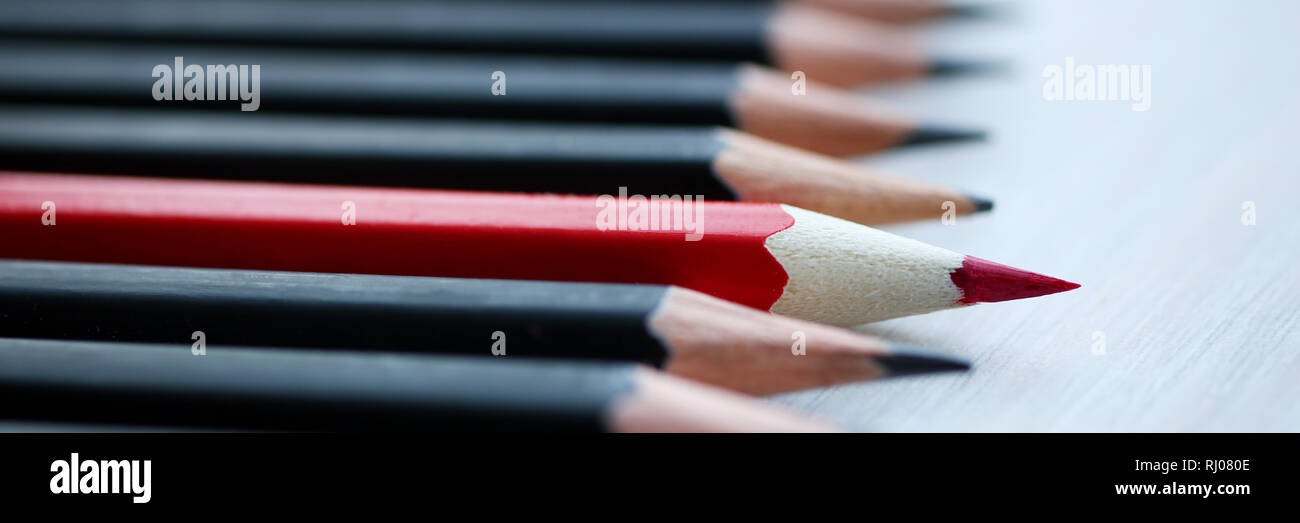 Red pencil standing out from crowd of - Stock Image