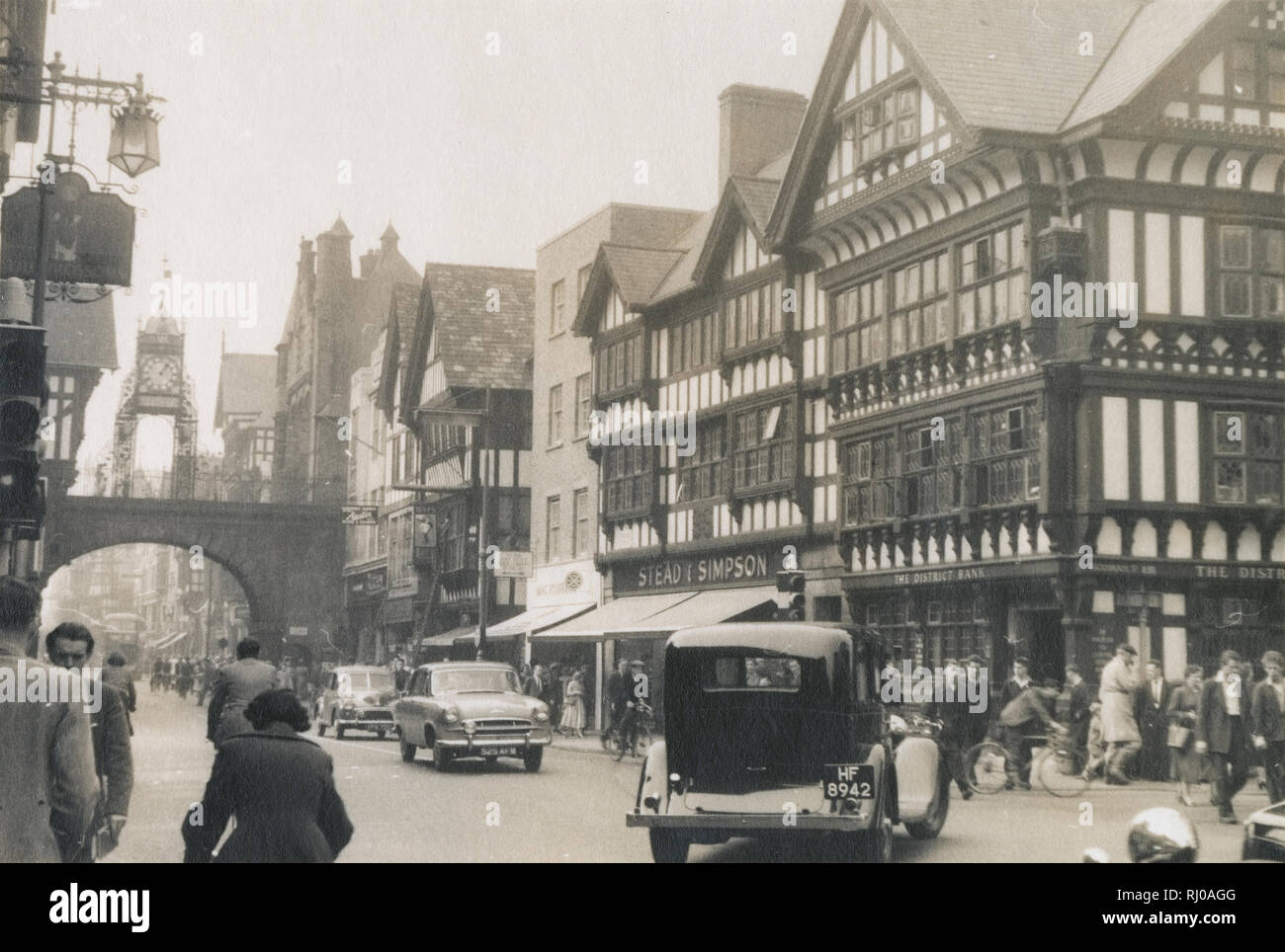 Antique c1950 photograph, the Eastgate Clock with shops and traffic on Foregate Street in Chester, England, UK. The shop Stead & Simpson is located at 11 Foregate St. SOURCE: ORIGINAL VINTAGE PHOTOGRAPH - Stock Image