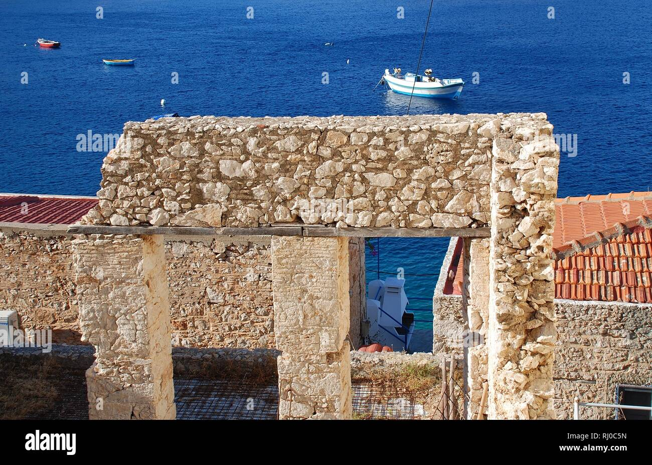 A derelict old stone building by the harbour at Emborio on the Greek island of Halki. - Stock Image