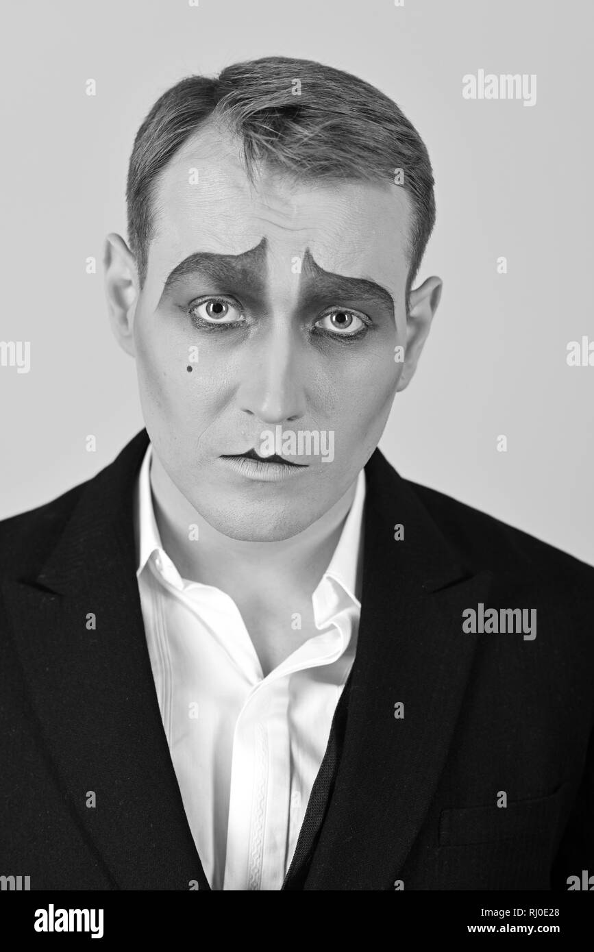 Tragical actor. Man with mime makeup. Mime artist. Mime with face paint. Theatre actor miming. Stage actor miming. Theatrical performance art and - Stock Image