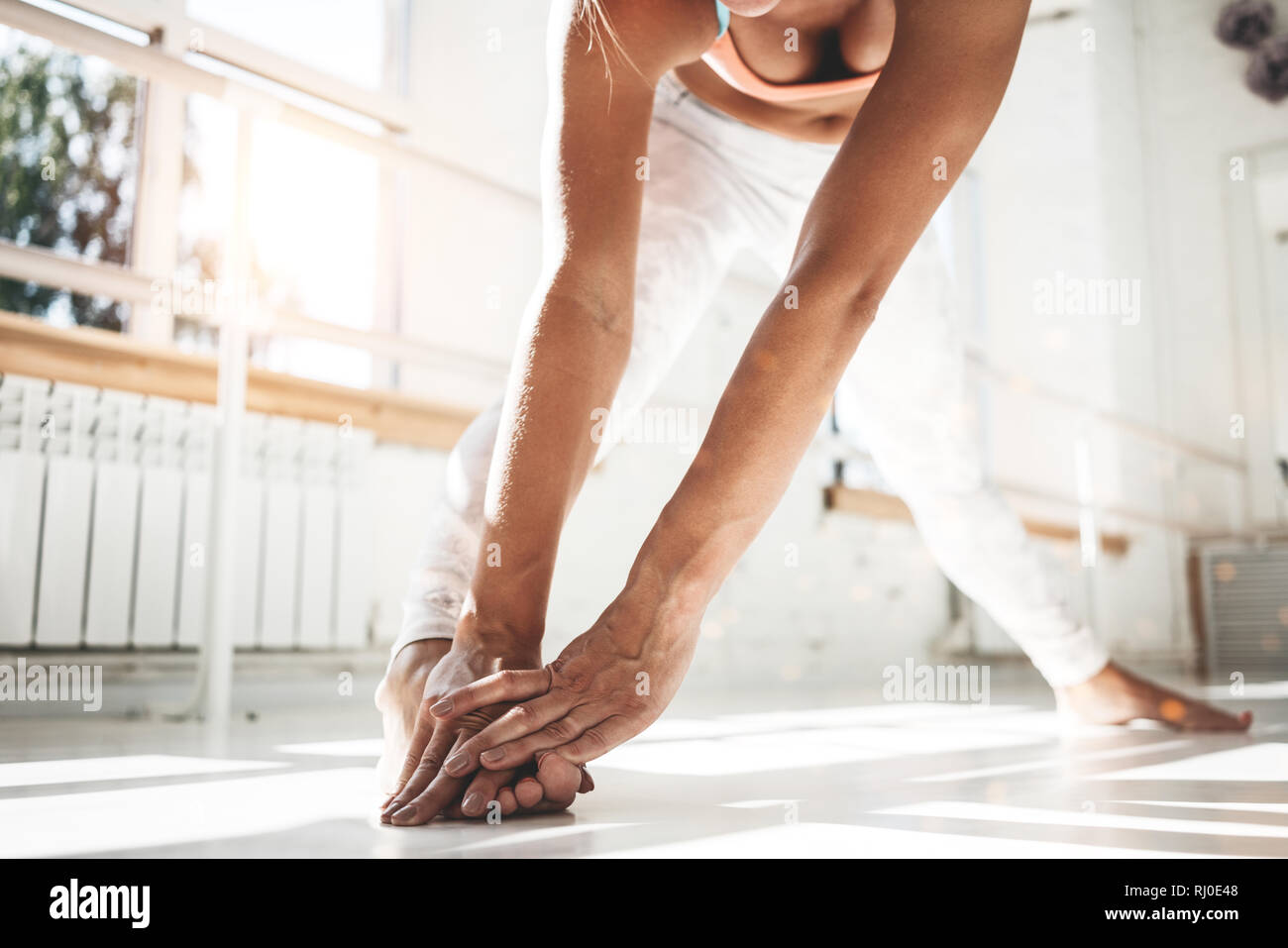 Closeup view on female athlet doing stretching exercises indoor sunny gym - Stock Image