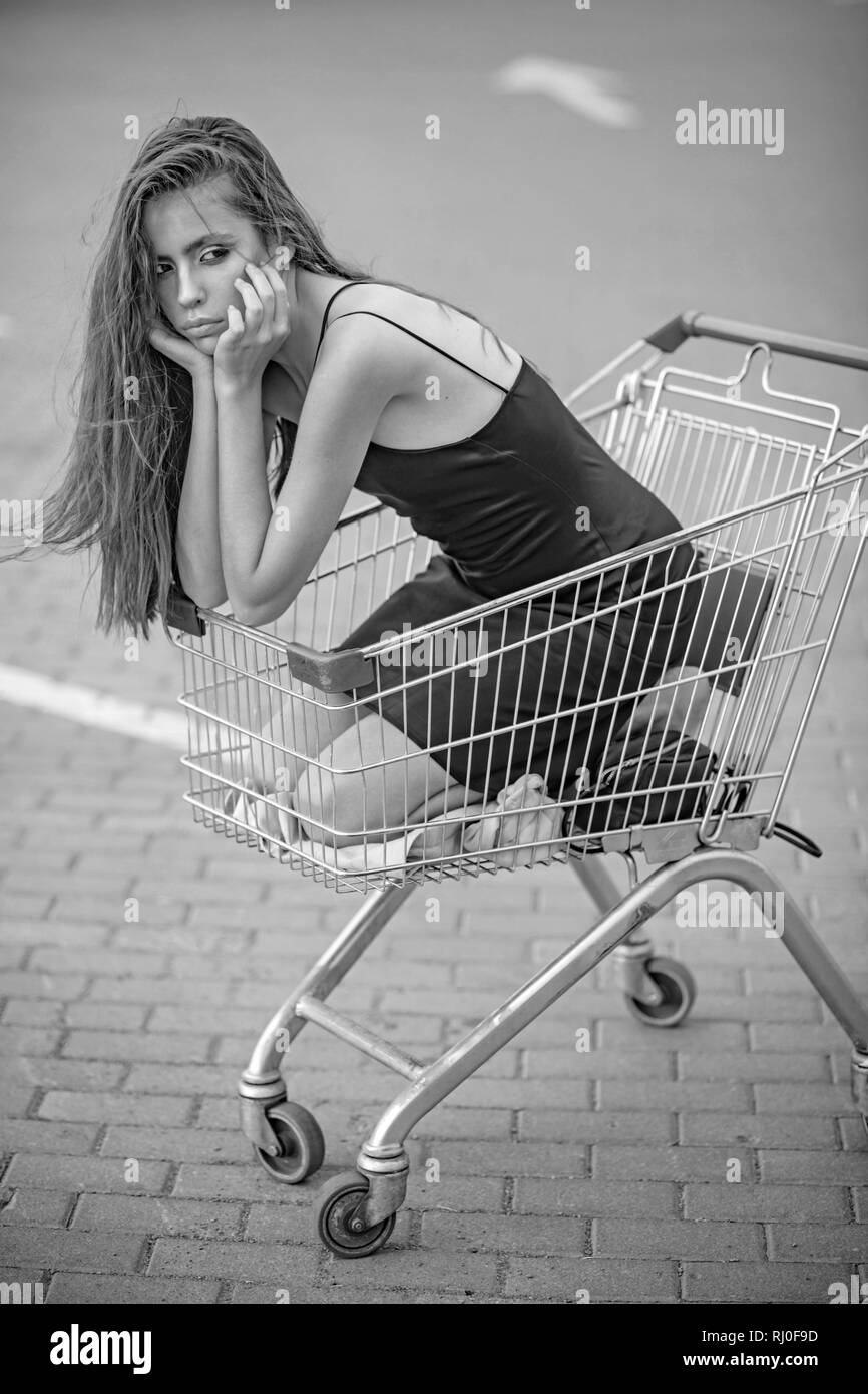 Sad girl in empty shopping trolley at market parking - Stock Image