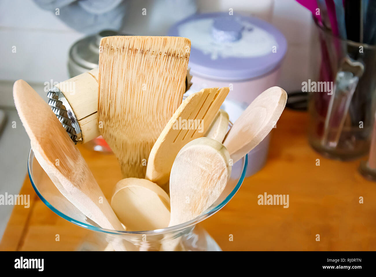 Wooden kitchen utensils in a glass container. Kitchen interior shot. Home decor and cooking concept Stock Photo
