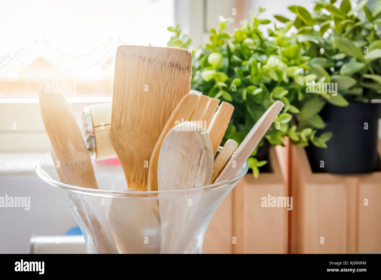 Wooden kitchen utensils in a glass container with a grass in the background. Kitchen interior shot. Home decor and cooking concept Stock Photo