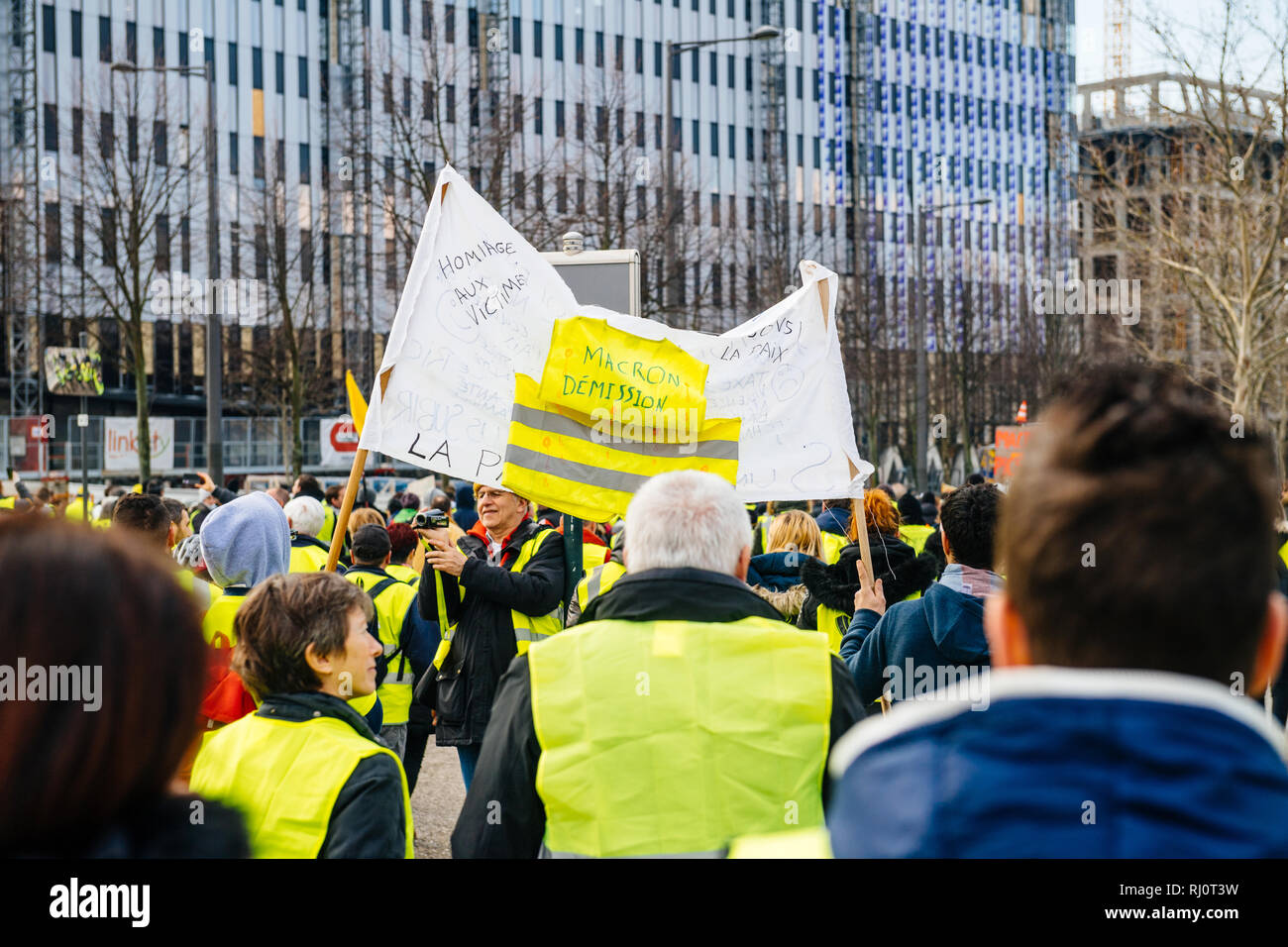 STRASBOURG, FRANCE - FEB 02, 2018: People demonstrating marching with placards during protest of Gilets Jaunes Yellow Vest placard with inscription Macron resignation  - Stock Image