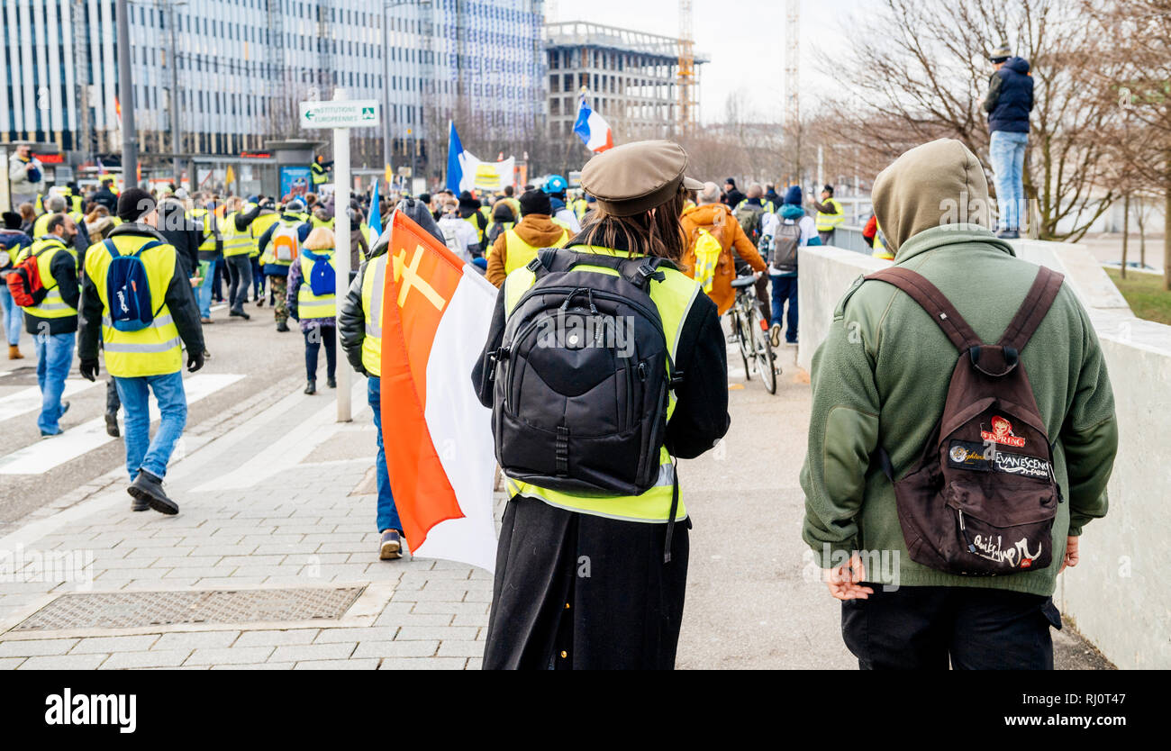 STRASBOURG, FRANCE - FEB 02, 2018: Man in russian revolution costume demonstrating walking with flags during protest of Gilets Jaunes Yellow Vest manifestation anti-government demonstrations on Boulevard de Dresde - Stock Image