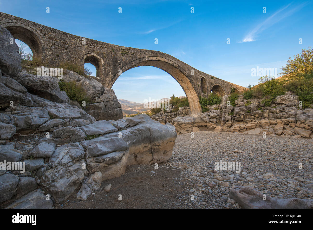 The Mesi bridge (Ura e Mesit) in Mes, Albania, near Shkoder . An old stone Ottoman bridge - the largest in the country. Dry river and mountains - Stock Image