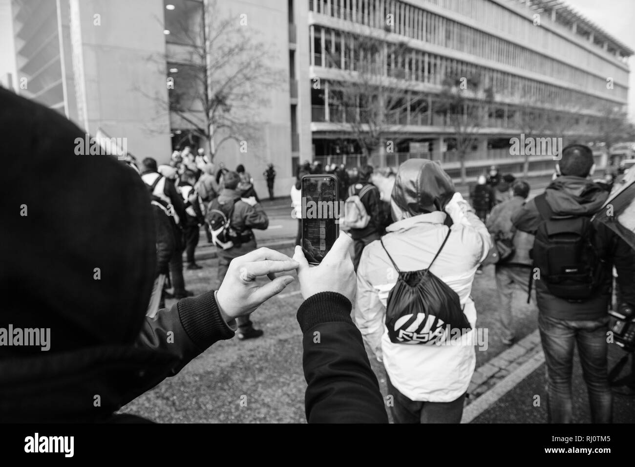 STRASBOURG, FRANCE - FEB 02, 2018: Man with mask taking footage of protesters and Police forces during protest of Gilets Jaunes Yellow Vest anti-government demonstrations - Stock Image