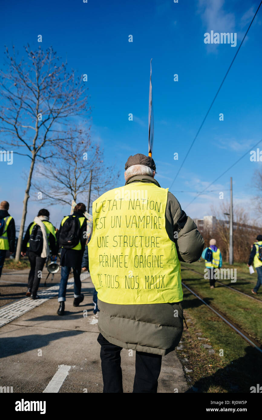 STRASBOURG, FRANCE - FEB 02, 2018: Man in Gilets Jaunes Yellow Vest with inscription the state is a vampire manifestation European Parliament against the expensive life - Stock Image
