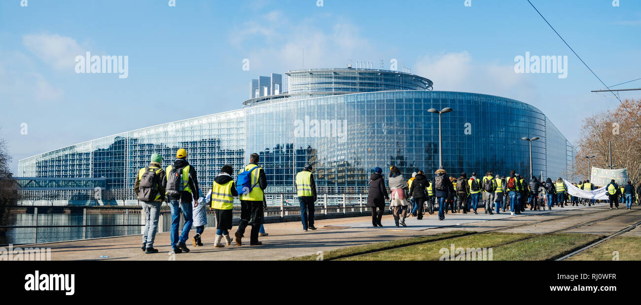 STRASBOURG, FRANCE - FEB 02, 2018: People demonstrating walking toward European Parliament during protest of Gilets Jaunes Yellow Vest manifestation anti-government demonstrations - Stock Image