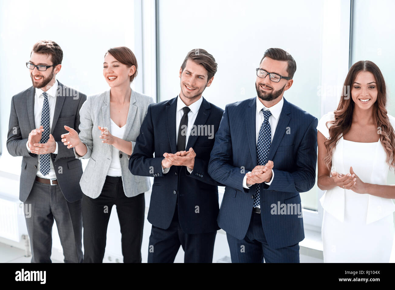 group of young business people applauding standing in the office. - Stock Image