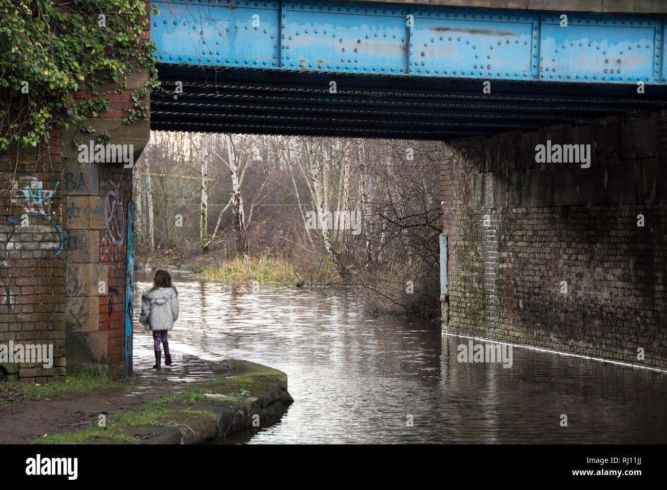 Sheffield, UK – January 24 2016 : A young girl walks beneath Pothouse Bridge on the Sheffield and Tinsley Canal, Coleridge Road - Stock Image