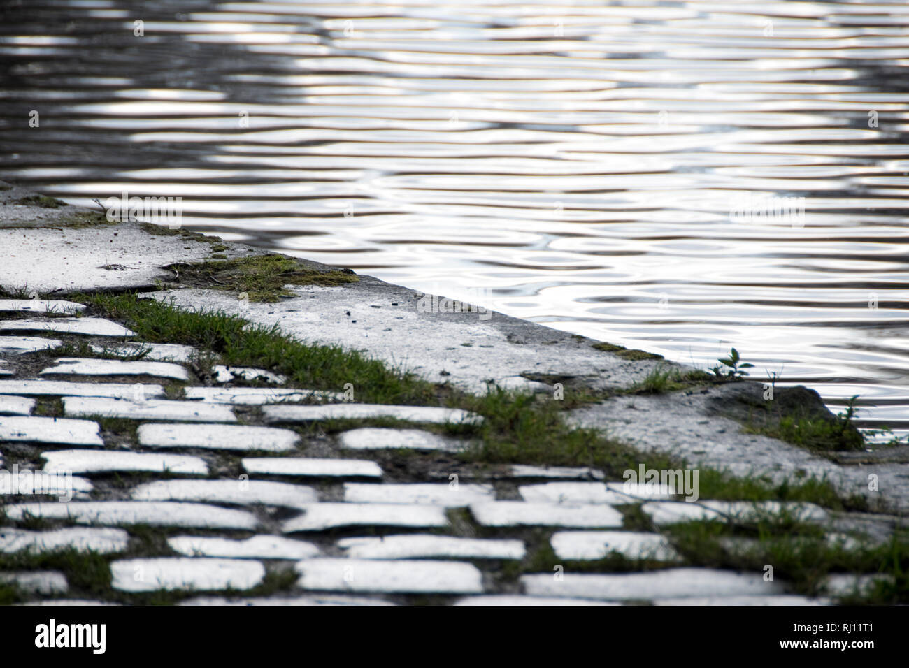 Wet cobblestones and ripples in the water of the Sheffield and Tinsley Canal, wet winter day abstract - Stock Image